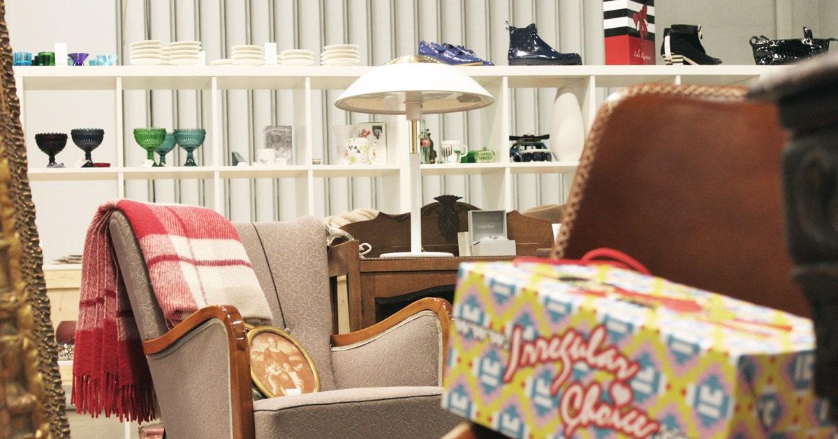 Messuosastolla vanha nojatuoli, lamppu, kenkälaatikko ja taustalla kenkiä ja lasiesineitä hyllyillä.
