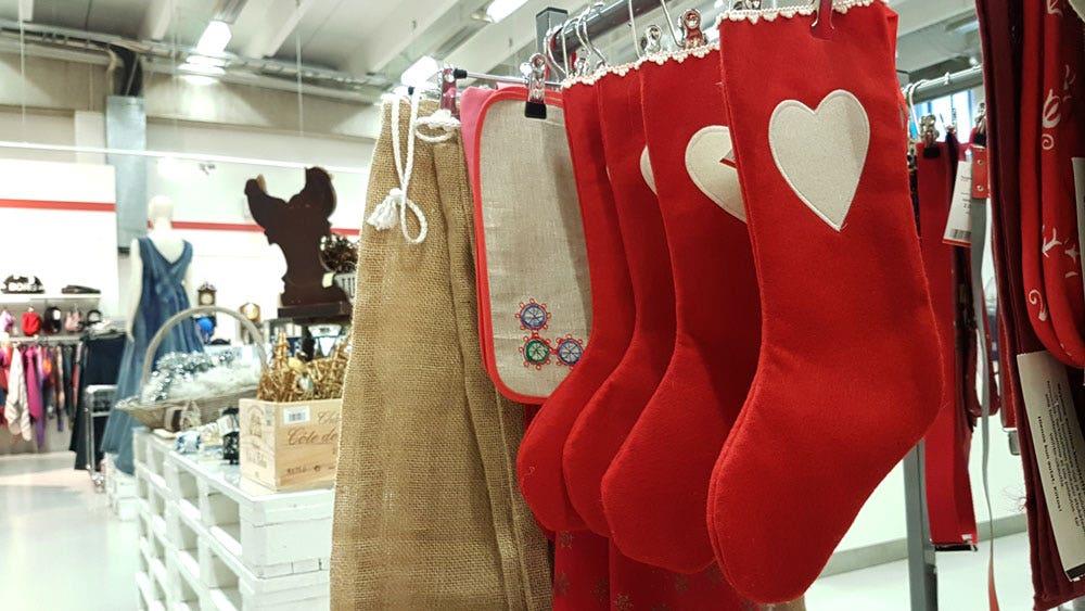Punaisia joulusukkia roikkumassa vaaterekissä. Taustalla Kontti-myymälää, jouluvalikoimaa ja farkusta tehty iltapuku.