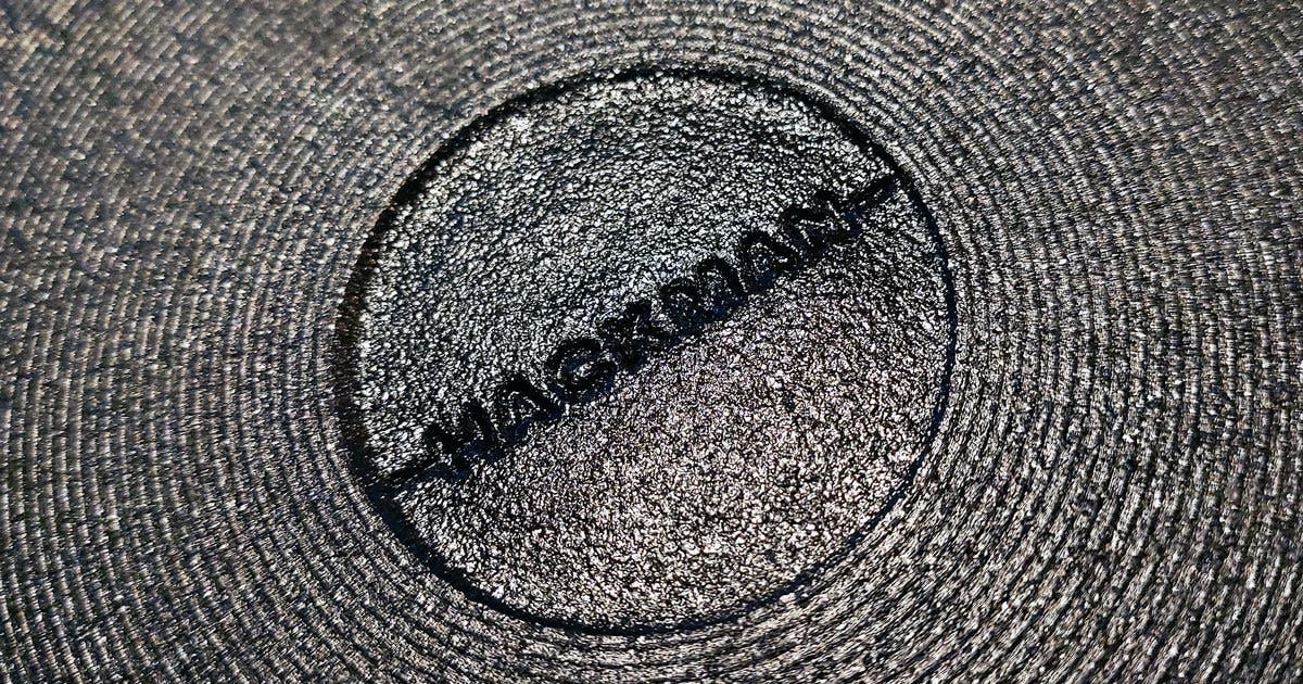 Hackmanin logo mustan valurautapannun pohjassa
