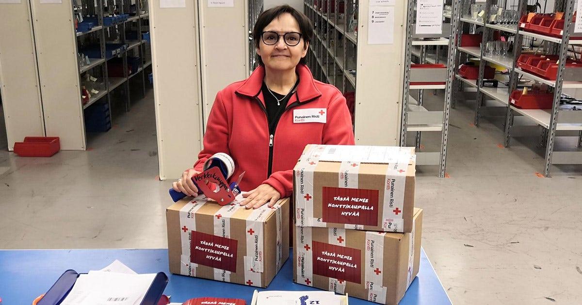 Henkilö pakkaamassa postipaketteja varastolla, taustalla varastohyllyjä täynnä tavaraa